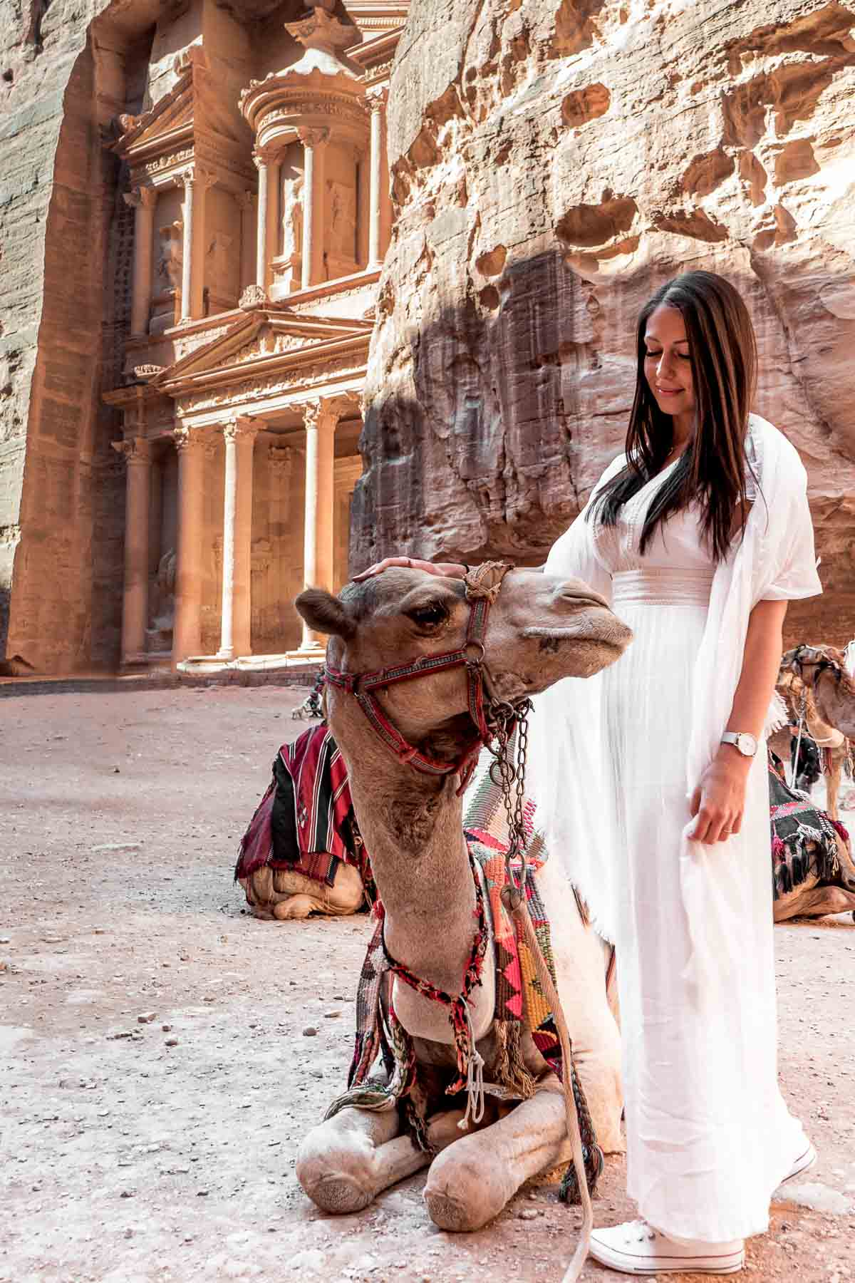 Girl in a white dress standing next to a camel with the Treasury in the background at Petra, Jordan
