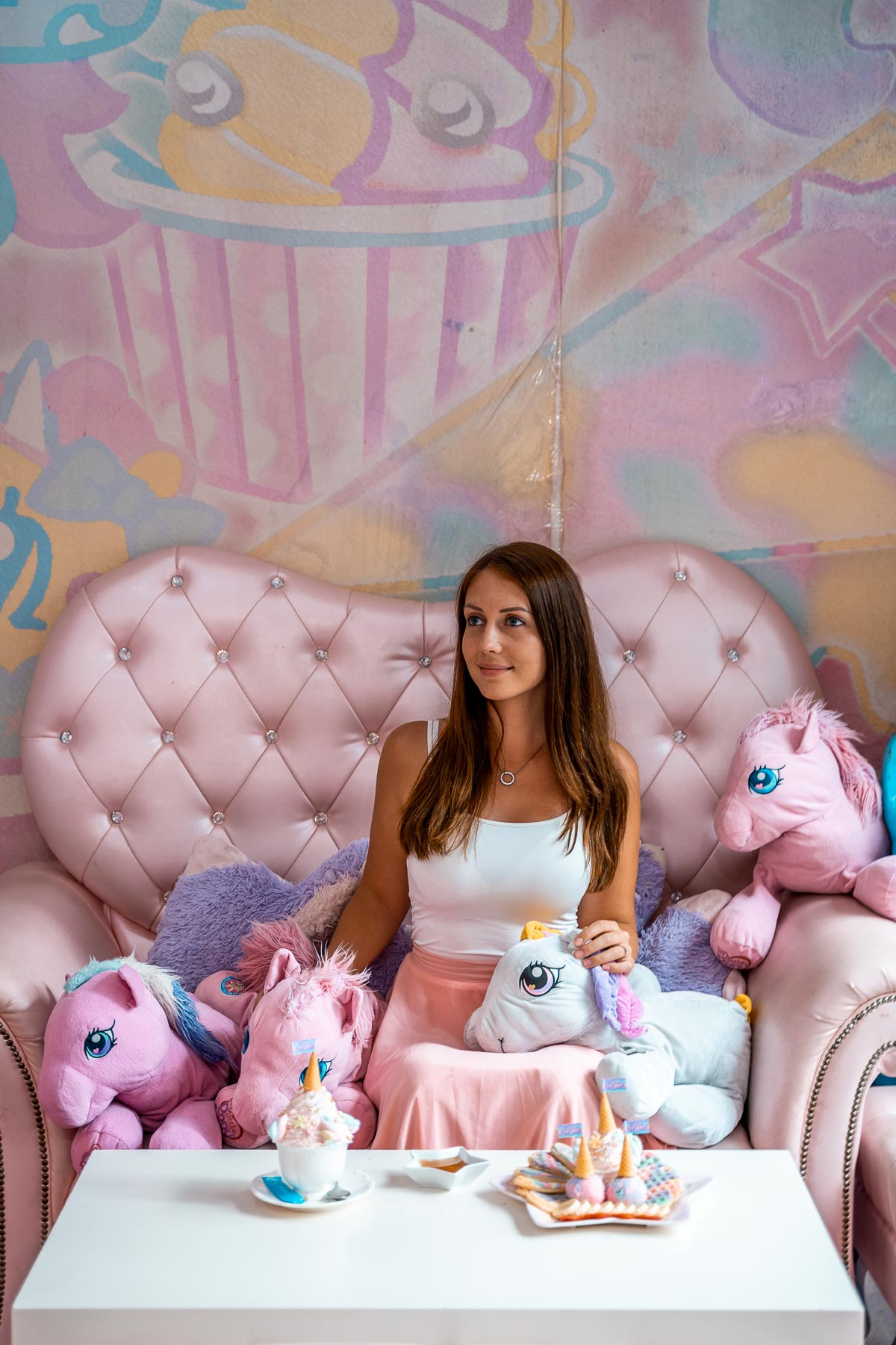 Girl in a pink-white dress sitting in a pink chair with plush unicorns at the Unicorn Cafe in Bangkok
