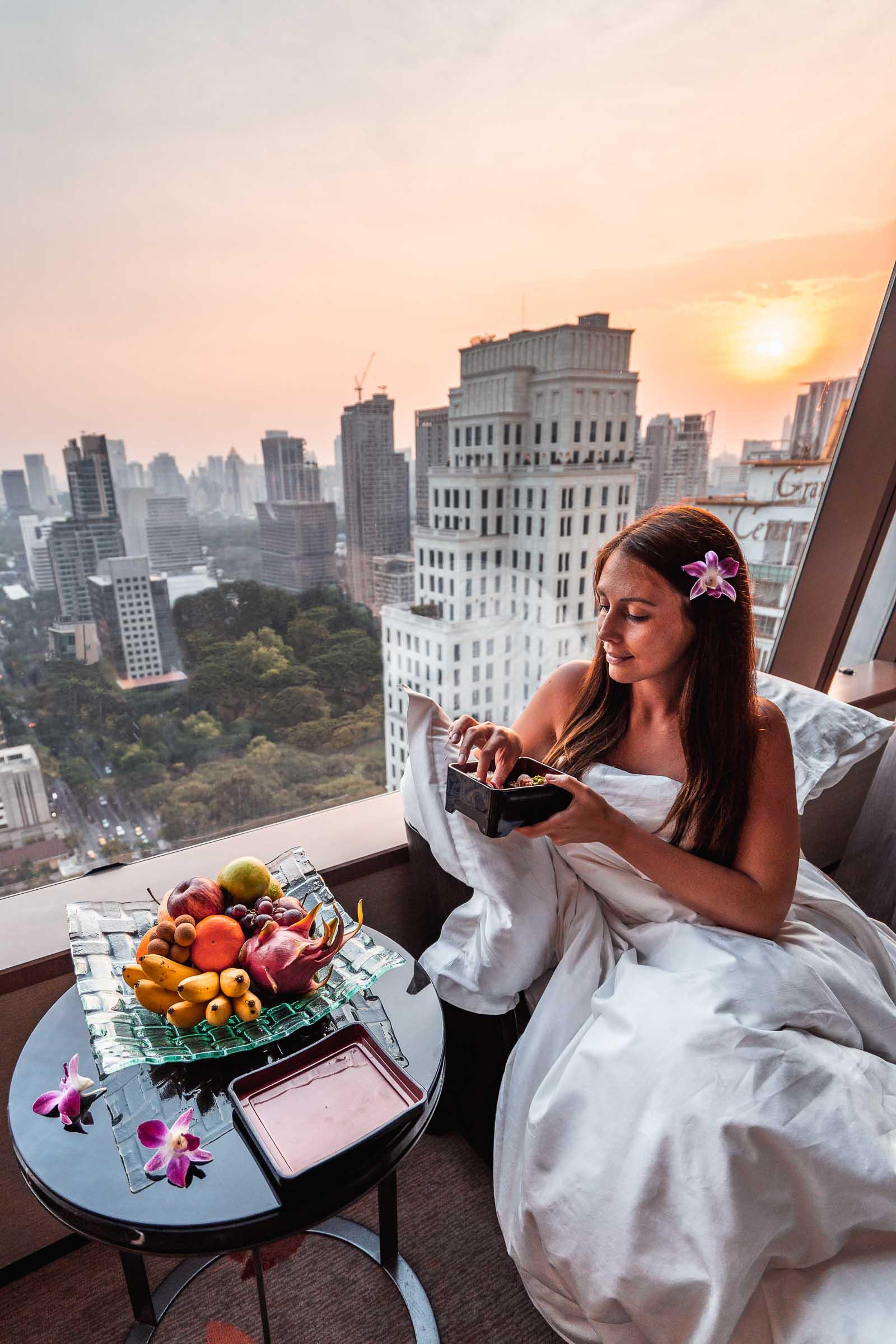 Girl eating breakfast with a view of the Bangkok skyline in the background in The Okura Prestige Bangkok