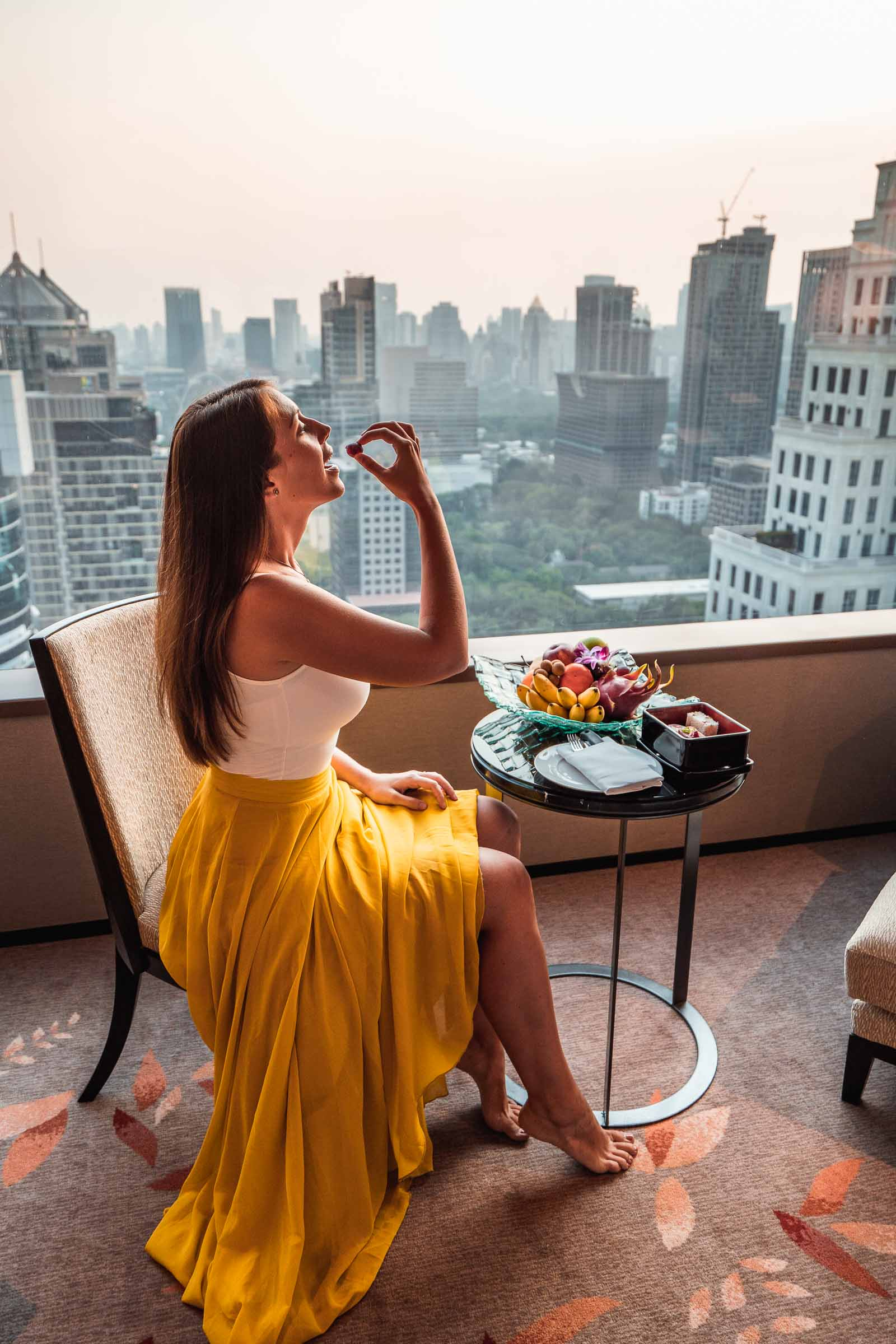 Girl in a yellow skirt sitting in one of the rooms of The Okura Prestige Bangkok enjoying the view