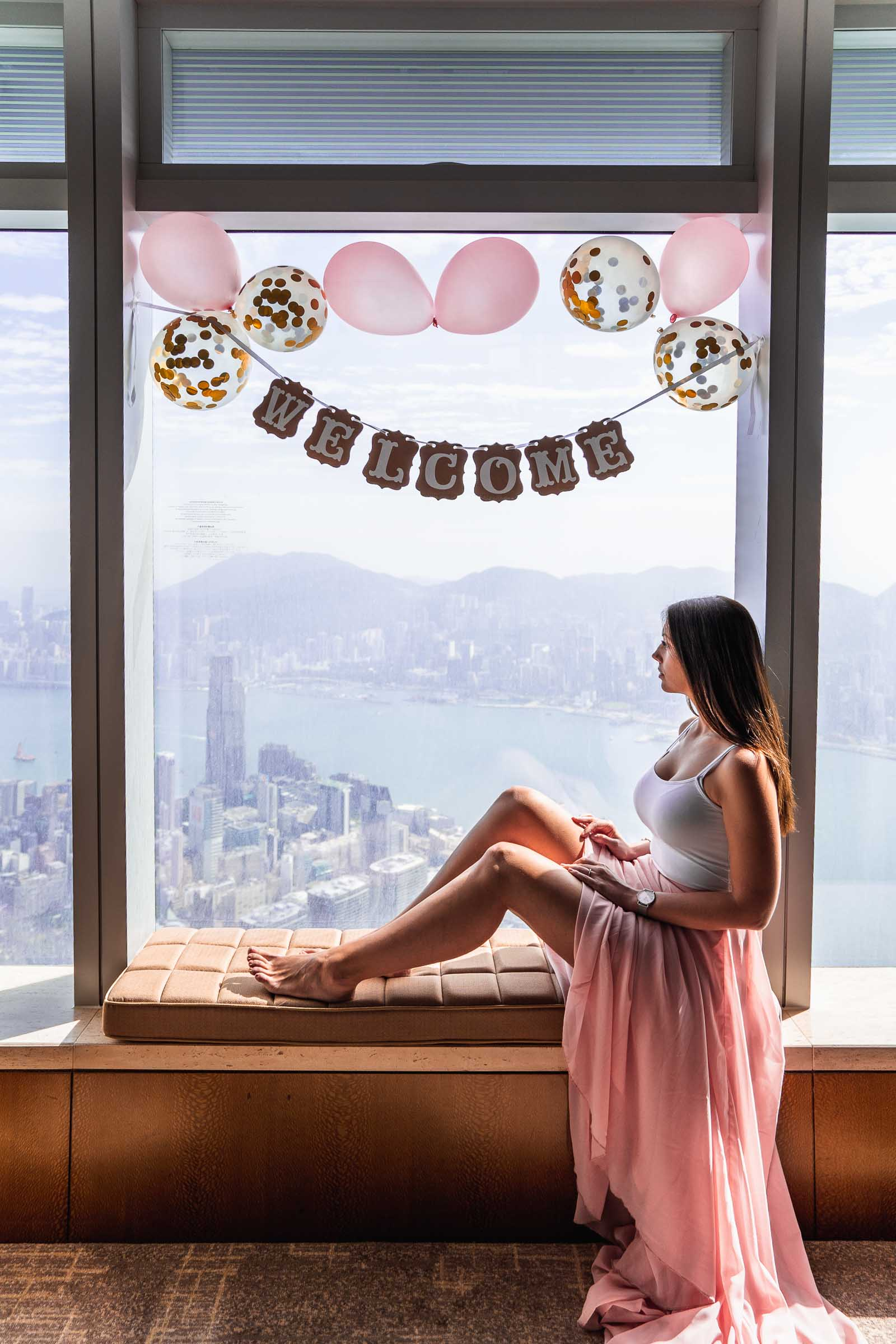 Girl in pink skirt sitting in the window looking over the Victoria Harbour in Hong Kong