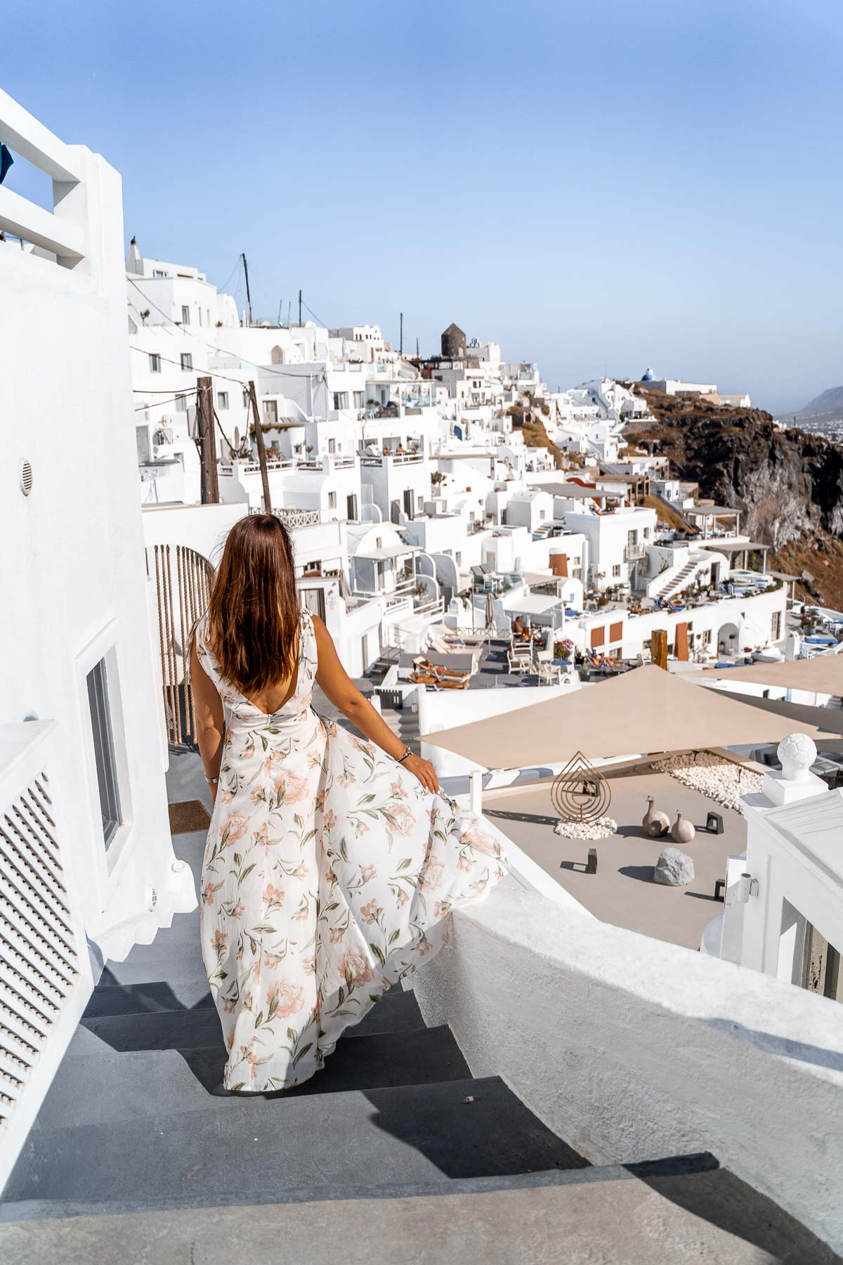 Girl in a floral dress standing in the streets of Imerovigli, Santorini