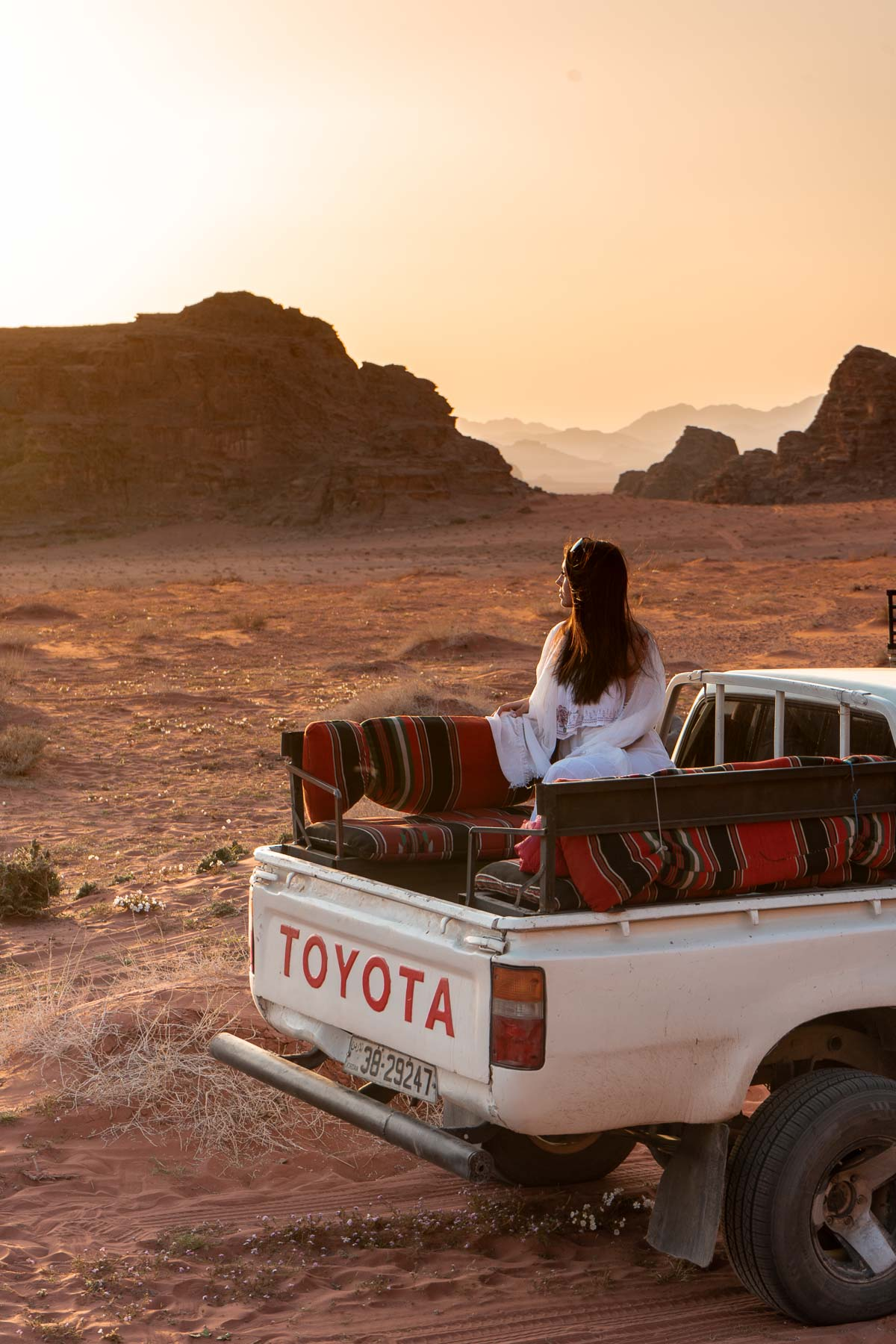 Girl in a white dress watching the sunset in a pick-up truck in the Wadi Rum, Jordan