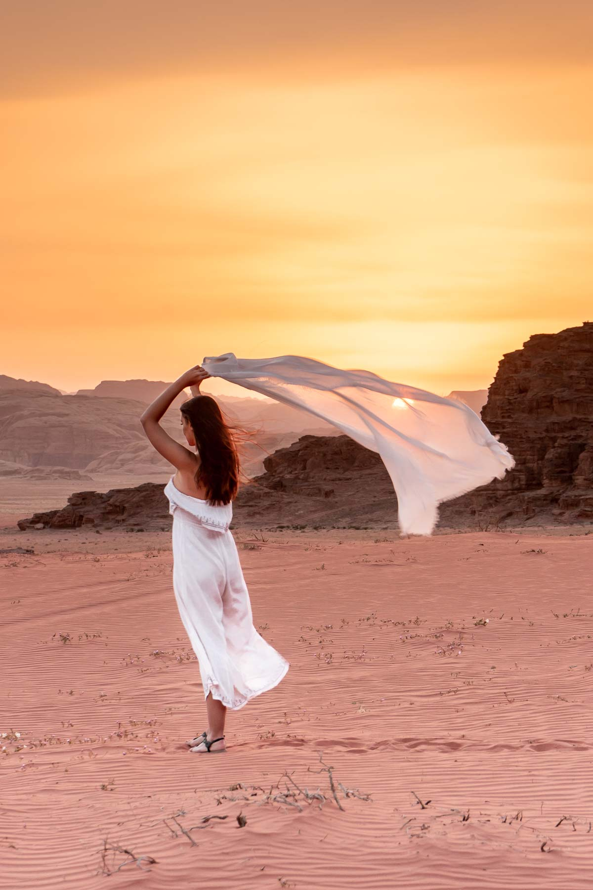 Girl in a white dress watching the sunset in the Wadi Rum, Jordan