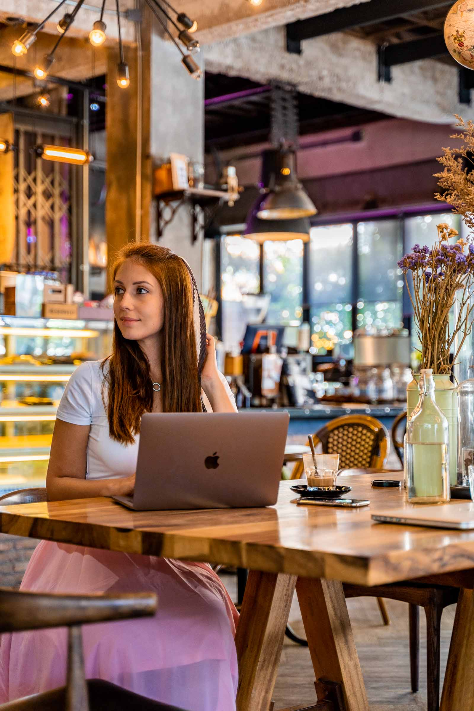 Girl sitting in front of a laptop at Artisan Cafe in Chiang Mai