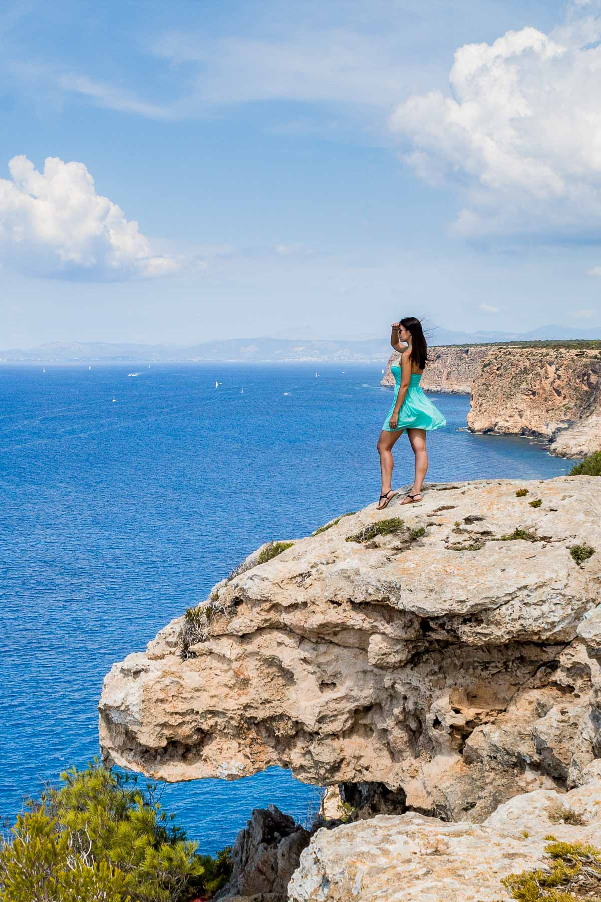 Girl in a blue dress standing on a rock at the coastline of Mallorca